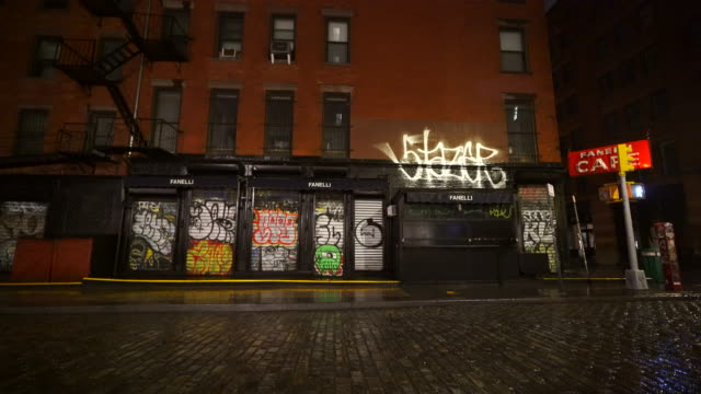 stockvideo's en b-roll-footage met people disappeared from town in the rainy night for impact of covid-19 in soho district new york city ny usa on mar. 19 2020. - bar gebouw