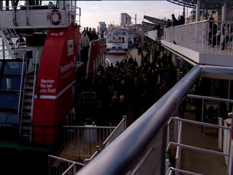 People disembark from ferry seconds after docking large crowd wait to board Hamburg