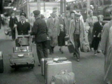 people disembark trains and carry their luggage along the platforms at dover railway station. 1954. - bahnreisender stock-videos und b-roll-filmmaterial