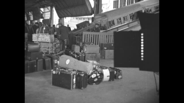stockvideo's en b-roll-footage met people disembarking via ship's gangplank / vs mounds of luggage on docks world's fair sticker on bags / tugboats at side of the ocean liner oslofjord... - vorst
