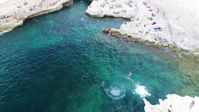 people diving into st.peter's pool, marsaxlokk, malta - rock face stock videos & royalty-free footage