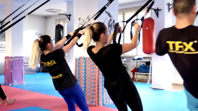 People doing arm exercises with suspension straps