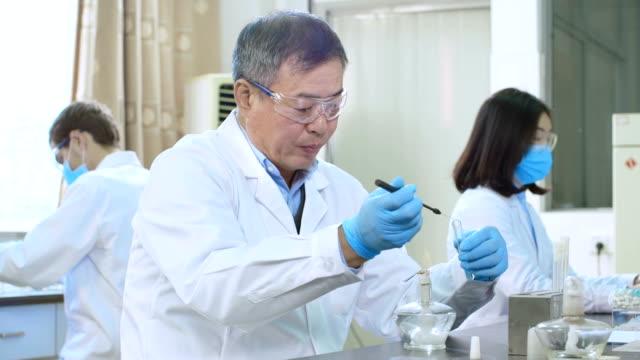 persone facendo esperimenti in laboratorio chimico 4 k - scienziata video stock e b–roll