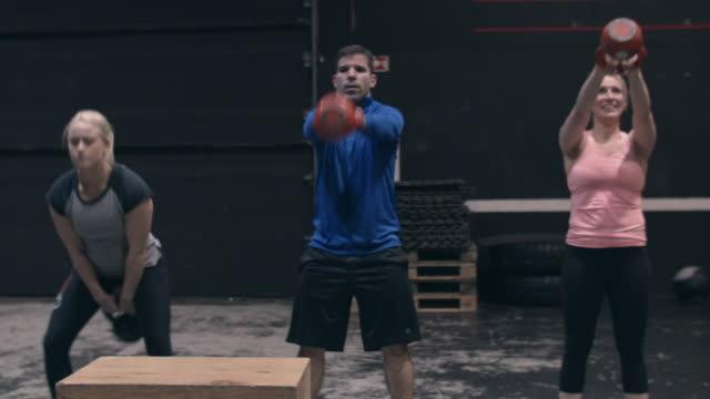 vídeos de stock, filmes e b-roll de people doing kettle bell swings in a gym gym - calções de corrida