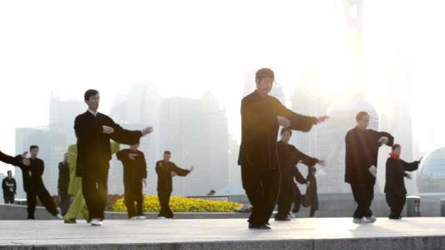 people doing tai chi on the bund, shanghai, china - lehrerin stock-videos und b-roll-filmmaterial