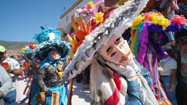 people donning creative colorful costumes at zoque coiteco carnival parade in chiapas, mexico - chiapas stock-videos und b-roll-filmmaterial