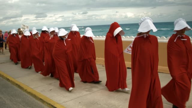People dressed as handmaidens protest against President Donald Trump on the one year anniversary of his inauguration on January 20 2018 in Palm Beach...