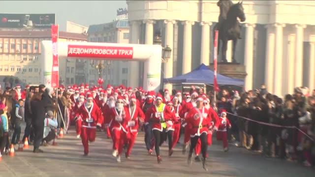 people dressed as santa claus take part in the santa claus race in skopje macedonia on december 27 2015 - skopje stock videos and b-roll footage