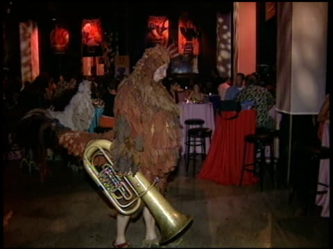 people dressed in chicken costumes holding tuba and saxophone walking around dance floor guest sitting at tables in bg - brass instrument stock videos & royalty-free footage