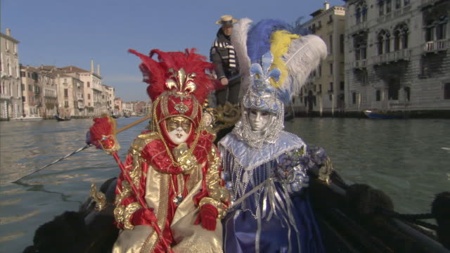 MS POV People dressed in lavishly decorated costumes traveling in gondola in canal, Gondolier rowing / Venice, Veneto, Italy