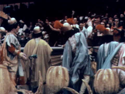 1960 montage ms people dressed in roman togas on parade float throwing things to spectators / ms people dressed as 'local yokels' on parade float / usa - traditional helmet stock videos and b-roll footage