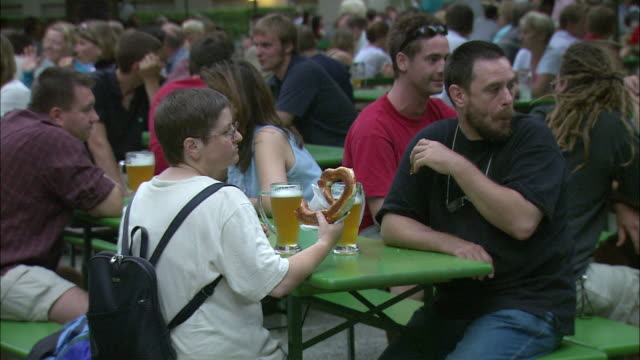 MS People drinking beer, eating pretzels and talking at Beer garden, Englischer Garten (English Garden), Munich, Bavaria, Germany