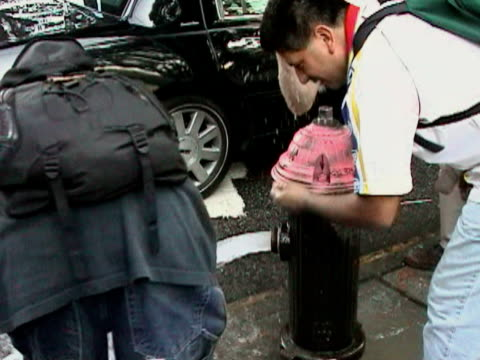 vídeos y material grabado en eventos de stock de people drinking water from fire hydrant during citywide blackout on august 14, 2003 / queens, new york, usa / audio - boca de riego