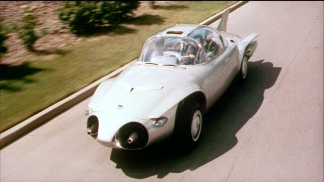 1958 POV HA People driving futuristic car on road / USA / AUDIO