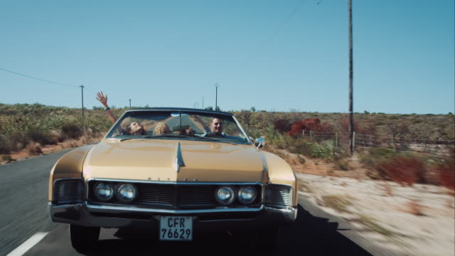 people driving in retro car on outback road - retro convertible stock videos & royalty-free footage