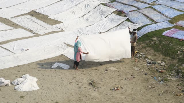 people Drying cloth on banks of River Yamuna, Agra,India