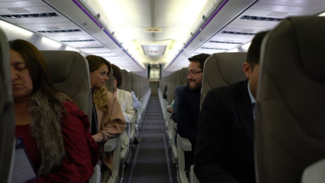 people during a commercial flight some talking others relaxing - abitacolo video stock e b–roll