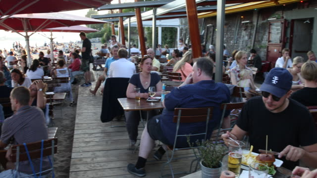 people eat at the beach and at a bar and restaurant at elbe river in hamburg harbour on a hot summer day with temperatures above 30 degrees during... - swimming shorts stock videos & royalty-free footage