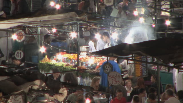 ms ha pan people eating at food stalls in overcrowded djemaa el fna square, marrakech, morocco - tradition stock videos & royalty-free footage