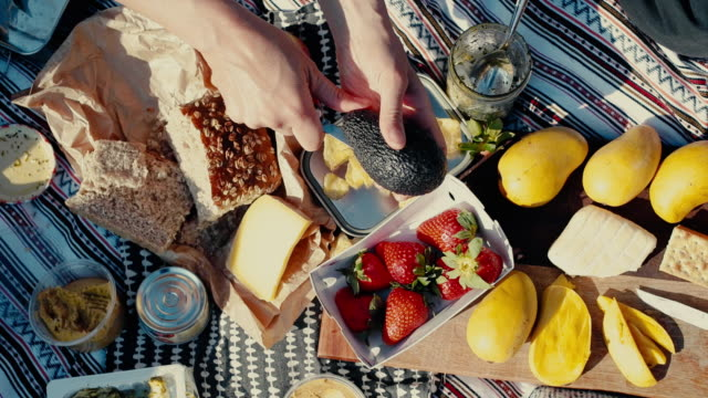 people eating colorful picnic with fruit and bread - food stock videos & royalty-free footage