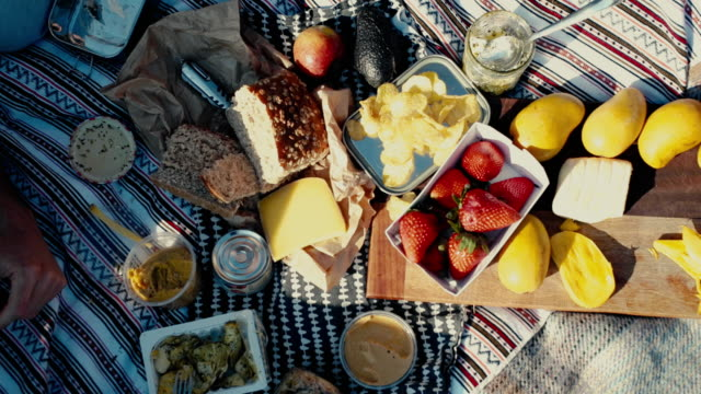 stockvideo's en b-roll-footage met people eating colorful picnic with fruit and bread - picknick