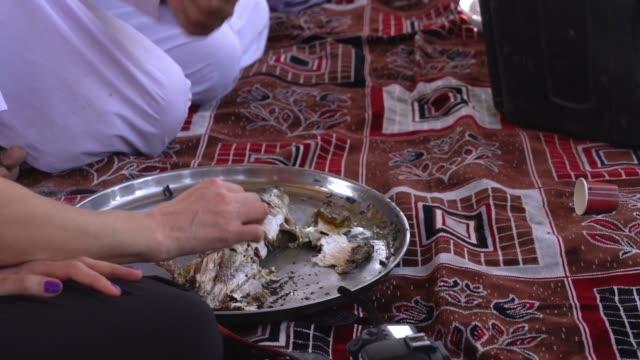 frau leute essen fisch, der nach traditionellem rezept aus dem nahen osten geröstet wird - oman stock-videos und b-roll-filmmaterial