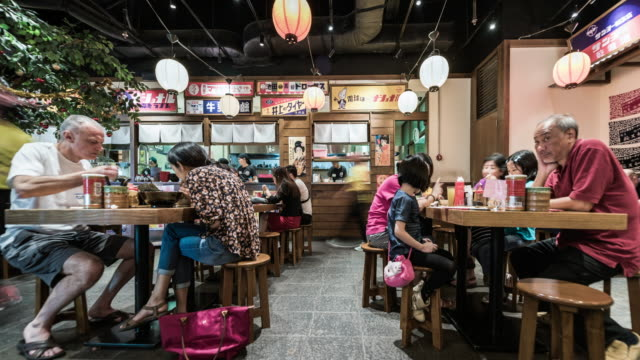 people eating inside a busy fast food noodle bar