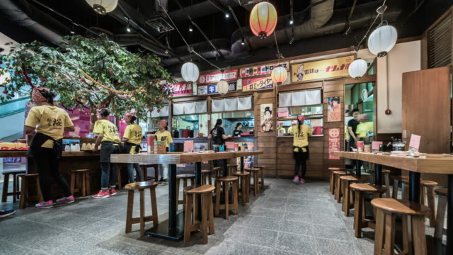 people eating inside a busy noodle bar