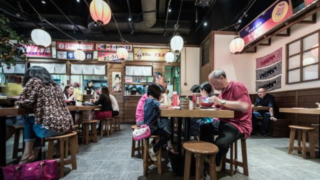 people eating inside a noodle bar