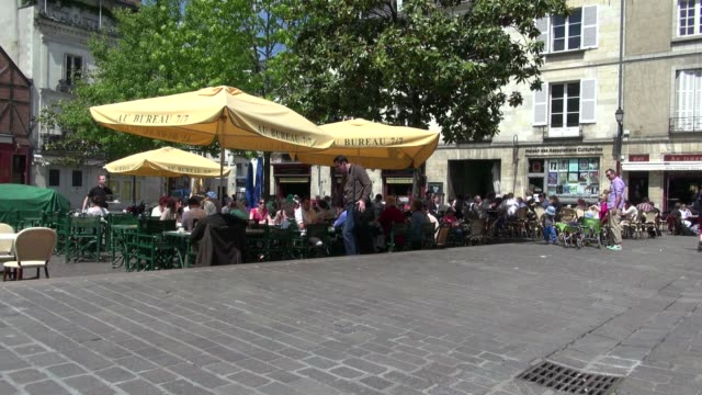 vídeos y material grabado en eventos de stock de people eating outdoors on a sunny day in place plumereau in the old town area of tours france the heart of chateaux country it produces some of the... - valle del loira