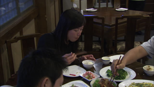 ms people eating together in restaurant, beijing, china - female with group of males stock videos & royalty-free footage
