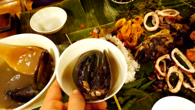 people eating with hands from a seafood plate served in a banana leaf in a restaurant - philippines stock videos & royalty-free footage