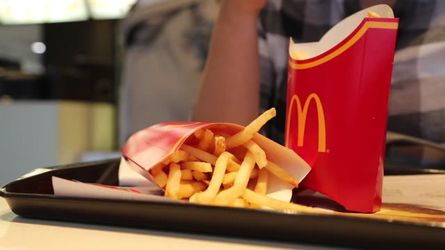 people eats fried chips in mcdonald's restaurant - mcdonald's stock videos & royalty-free footage