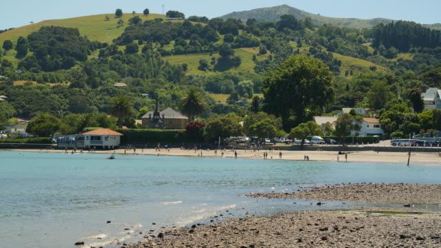 people enjoy a sunny day at akaroa beach - akaroa stock videos & royalty-free footage