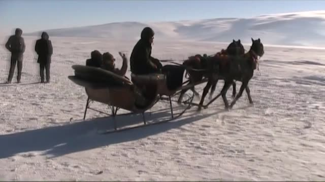 People enjoy horsedrawn sleigh sides on the frozen Lake Cildir in Aradahan province of Turkey on January 08 2017