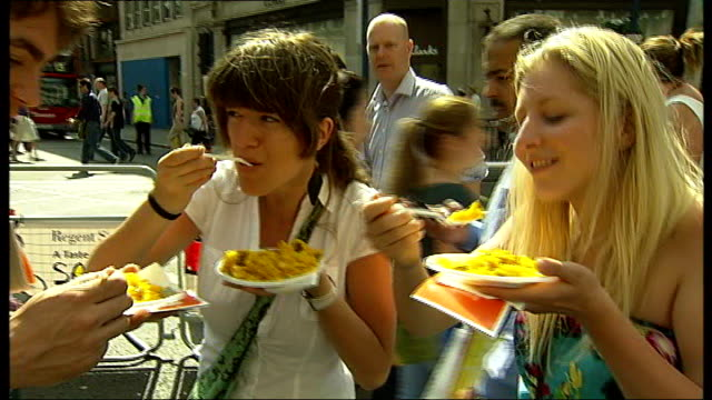 people enjoy hottest day of the year so far; london: regent street: **music heard sot** various of people enjoying the 'taste of spain' festival,... - パエリヤ点の映像素材/bロール