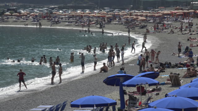 People enjoy on beach of Monterosso at the mediterranean sea