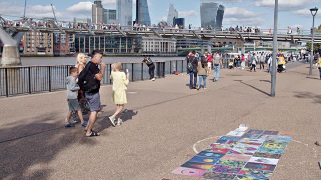 people enjoy outdoors by riverside. vendor sell art. walking bridge in distance. london skyline. - riverbank stock videos & royalty-free footage