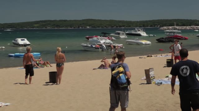 people enjoy summer activities at lake michigan beach in the summer - lakeshore stock videos & royalty-free footage
