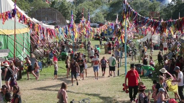 people enjoy the atmosphere at the glastonbury festival at worthy farm, pilton on june 27, 2015 in glastonbury, england. - お祭り好き点の映像素材/bロール