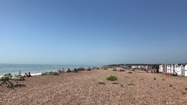 people enjoy the bank holiday sunshine on worthing beach in west sussex on bank holiday monday as temperatures reach 21 degrees. - worthing点の映像素材/bロール