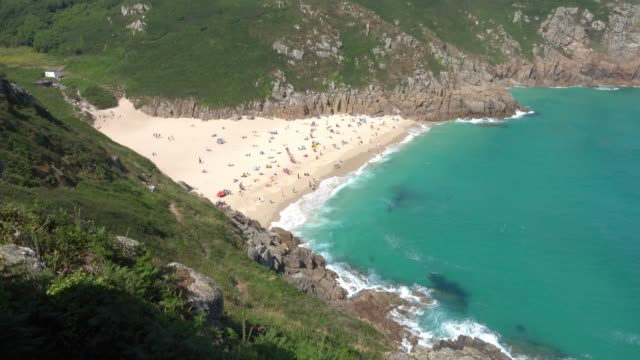 people enjoy the fine weather as they spend time on the beach at porthcurno beach near penzance on june 28 2018 in cornwall england parts of the uk... - cornwall england stock-videos und b-roll-filmmaterial