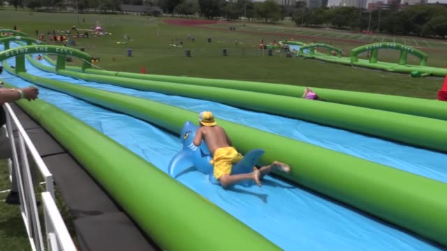 People enjoy the inflammable water slide during the 'Slide the City' water slide event at Montrose Park in Chicago on July 31 2016