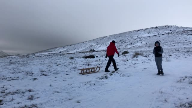 people enjoy the snow in the brecon beacons wales - ブレコンビーコンズ国立公園点の映像素材/bロール