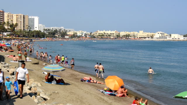 People enjoy the summer sun on the beach on July 23 2017 in Malaga Spain With Brexit discussions yet to provide answers to a number of questions...