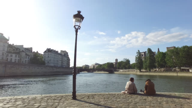 may 11: people enjoy the sun on the banks of the seine river at the end of ile saint louis, below place louis aragon, 75004 paris, as france is... - five people stock videos & royalty-free footage