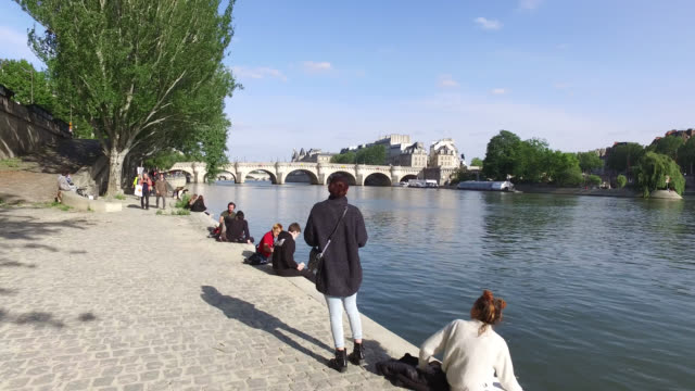 """may 11: people enjoy the sun on the banks of the seine river in front of the """"pont neuf"""" bridge as france is slowly reopening today after almost two... - ポンヌフ点の映像素材/bロール"""