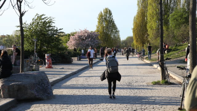 people enjoy the sunny and warm spring weather during the coronavirus crisis in the mauerpark in the district prenzlauer berg on april 18, 2020 in... - sunny video stock e b–roll