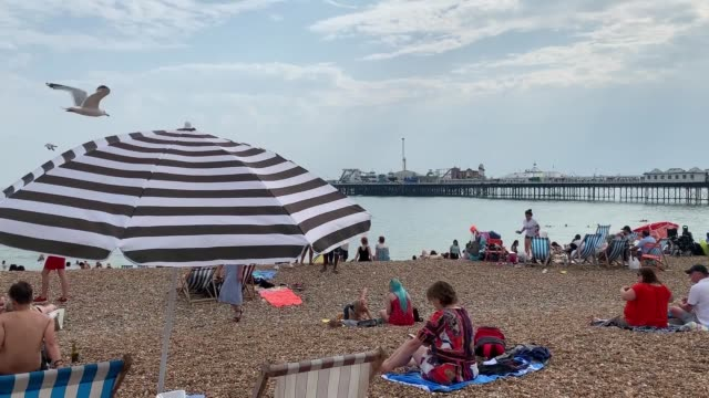 people enjoy the sunshine on brighton beach in east sussex as the uk has its hottest july day and second hottest day on record as the mercury hit... - no doubt band stock videos & royalty-free footage
