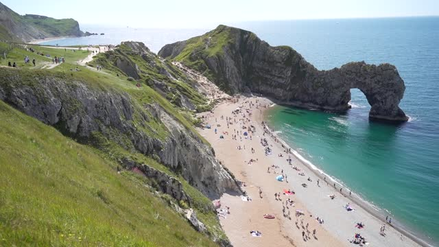people enjoy the warm weather on the beach at durdle door in dorset, on the first day of meteorological summer. it comes as the uk could see record... - arch stock videos & royalty-free footage